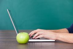 Person som använder bärbara datorn förutom det gröna äpplet Royaltyfri Foto