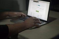 Person som använder bärbara datorn i mörkt rum Lynnigt illavarslande arkivbilder