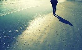 Person som bara går på den soliga sandiga stranden Arkivfoton