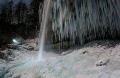 Person som exponerar den fryste vattenfallet Arkivbilder