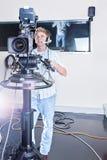 Person som fungerar en studiokamera, och klart att skjuta royaltyfri fotografi