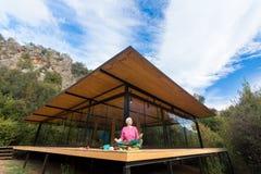 Person som gör yogaövning på träterrass av den lantliga kabinen Arkivfoto