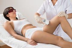 Person som ger laser-terapi till kvinnan Arkivfoto