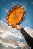 Person som i höjden rymmer en tamburin mot blå himmel Arkivbild