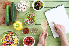 Person som rymmer träskeden och pekar på receptet i kokbok, medan laga mat arkivfoton