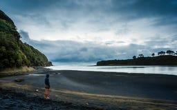 Person som ser thewater på en strand i Nya Zeeland Arkivbild