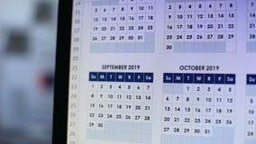 Person som ser till och med kalender på datoren som gör plan för det framtida året lager videofilmer