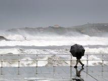 Person som skyddar med paraplyet i en regnig och blåsig dag royaltyfri bild