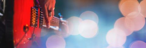 Person som spelar den elektriska gitarren med gula ljus arkivfoton