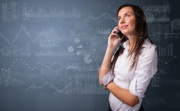 Person som talar på telefonen med diagrammet och rapporten i förgrunden royaltyfria bilder