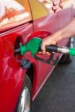 Person som tankar en bil på bensinstationen Arkivfoto