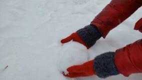 Person som tar snö från jordning som tycker om den härliga vinternaturen i skog arkivfilmer