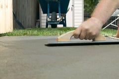 Person som troweling vått cement med konkret screed Royaltyfri Bild