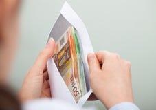 Person som ut kontrollerar kuvertet med kassa arkivbilder