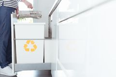 Person sorting paper in kitchen. Close-up of eco friendly person sorting paper in the kitchen into recycling container marked with yellow symbol royalty free stock photo