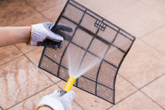 Person spraying water onto air conditioner filter to clean dust Stock Images