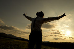 Person with spread arms in countryside sunset Royalty Free Stock Photo