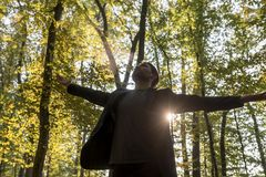 Person spreading out arms in woods Royalty Free Stock Photo