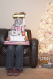 Person With Stack Of Christmas Gifts On Sofa Royalty Free Stock Photography