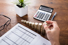 Person Stacking Coins On Desk Photos stock