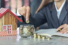 Person Stacking Coins Near House op Houten Bureau Onroerendgoedbelasting stock afbeelding
