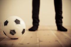 Person Standing Behind Soccer Ball no assoalho de madeira Fotografia de Stock