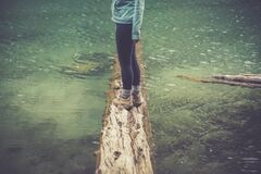 Person Standing on a Brown Wood Log Floating on a Body of Water Royalty Free Stock Photos
