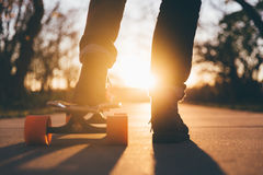 Person Standing on Concrete Pavement With Left Foot on Skateboard during Sunset Stock Images