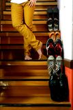 Person standing cross legged beside Different shoes on a staircase Stock Images