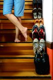 Person standing cross legged beside Different shoes on a staircase Royalty Free Stock Images