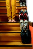 Person standing beside Different shoes on a staircase Royalty Free Stock Photos