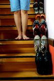 Person standing beside Different shoes on a staircase Royalty Free Stock Images