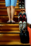 Person standing beside Different shoes on a staircase Stock Image