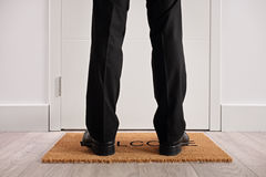 Person standing on a doormat in front of closed door. Person standing on a doormat with the word welcome written on it in front of a closed door Royalty Free Stock Photos