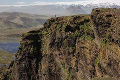 Man walking on large iceland cliff in dramatic landscape stock photos