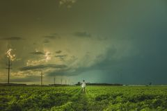 Person Standing on Green Plant Field Under Dark Heavy Clouds during Daytime Royalty Free Stock Photo