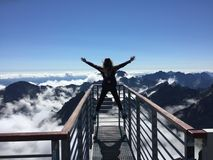 Person Standing on Hand Rails With Arms Wide Open Facing the Mountains and Clouds stock photos