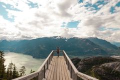 Person Standing With Hands on Air on Brown Wooden Dock With Overlooking View of Lake Under White Clouds and Blue Sky royalty free stock image