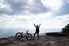 A person standing with hands up beside a bicycle on rocky mountain looking out at scenic. Natural view and beautiful blue sky royalty free stock photos