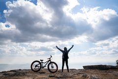 A person standing with hands up beside a bicycle on rocky mountain. Looking out at scenic natural view and beautiful blue sky royalty free stock images