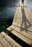 Person Standing On Jetty. Distance shot of a person standing on wooden jetty by peaceful lake Royalty Free Stock Photo