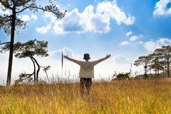 A person standing in large field enjoying the nature under beautiful blue sky royalty free stock photography