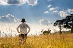 A person standing in large field enjoying the nature under beautiful blue sky stock image