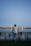 Person Standing and Leaning on Concrete Wall Facing Ocean and Skyline at Dawn Stock Images