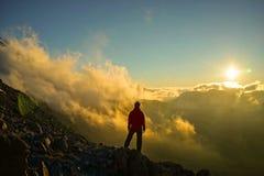 Person Standing na montanha com as nuvens durante o por do sol/Sunr imagens de stock royalty free