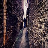 A person standing in a narrow pathway between two brick walls royalty free stock photos