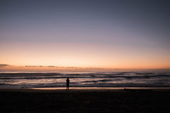 Person Standing Near the Shore during Sunset Stock Photos