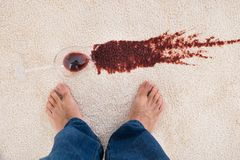 Person standing near wine spilled on carpet Royalty Free Stock Images