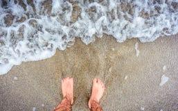 Person standing in ocean sea waves on sandy beach. Barefoot legs soaking in sea water. Man feet standing on sandy beach of Atlantic ocean in Galicia - Spain Stock Image