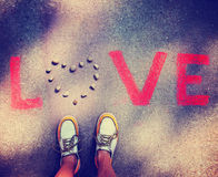 A person standing over the word love on a sidewalk Stock Images